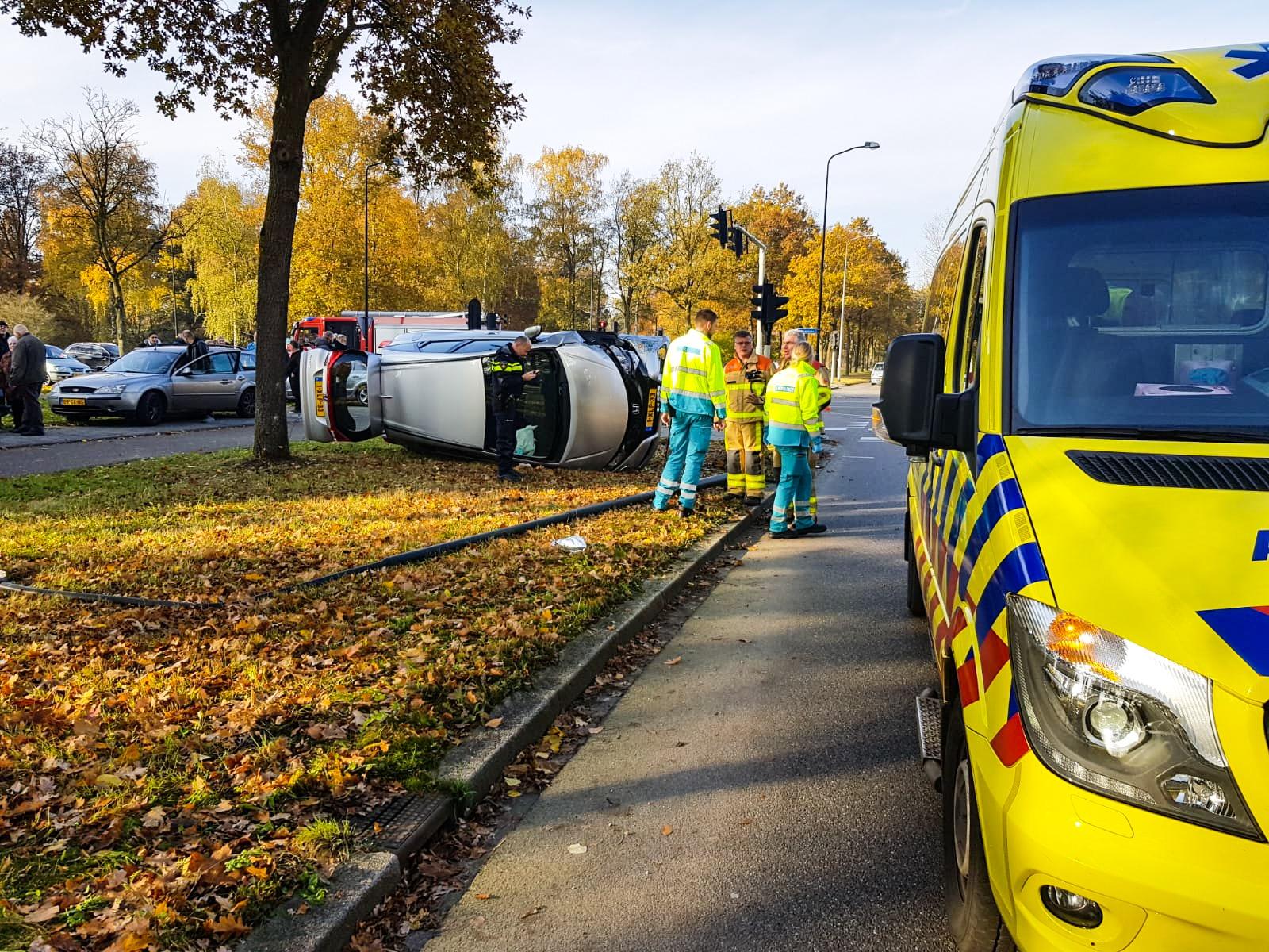 Auto belandt op zijn zijkant na botsing met andere auto.