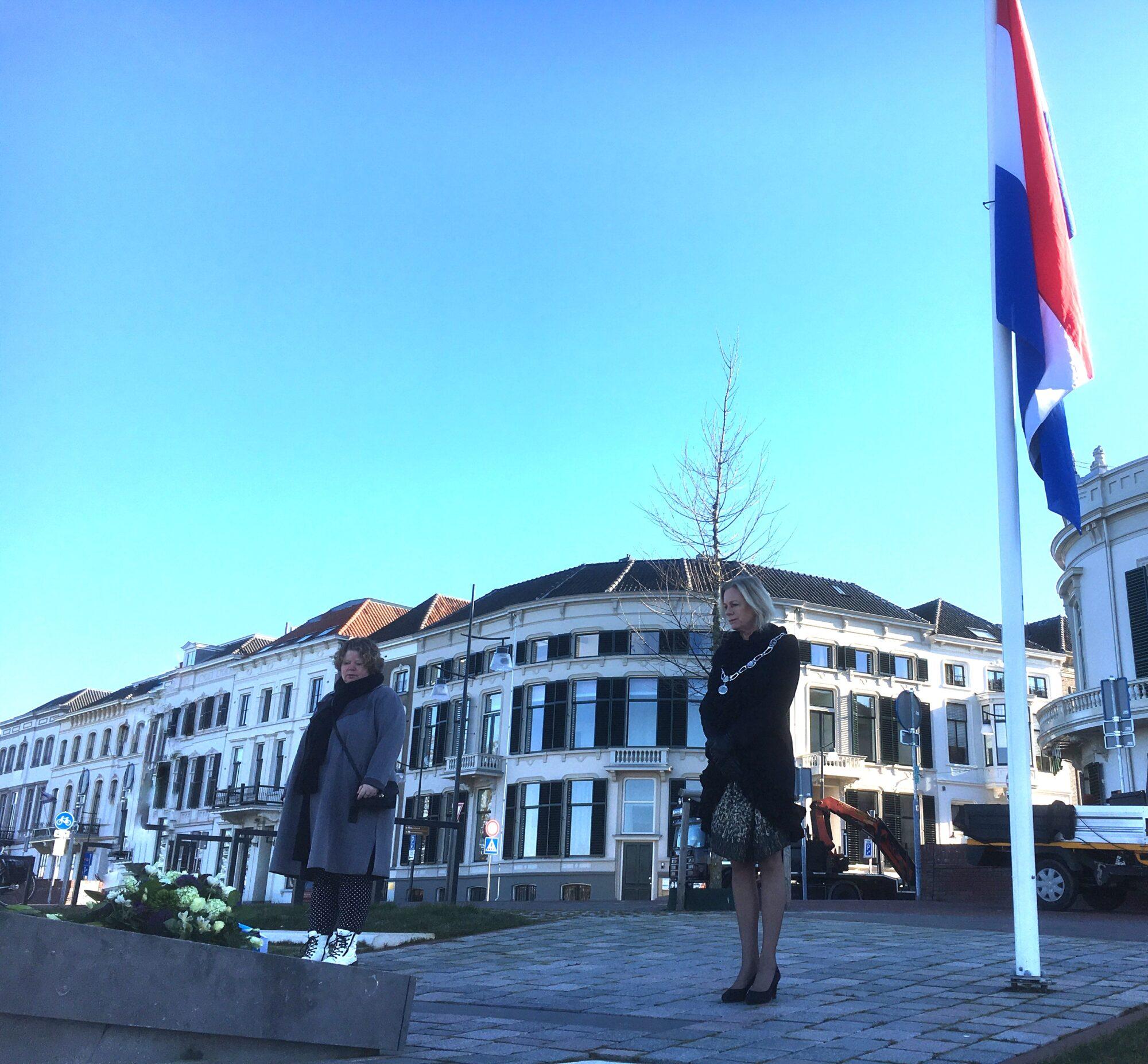 Burgemeester en directeur de Bongerd leggen bloemen bij monument op de IJsselkade