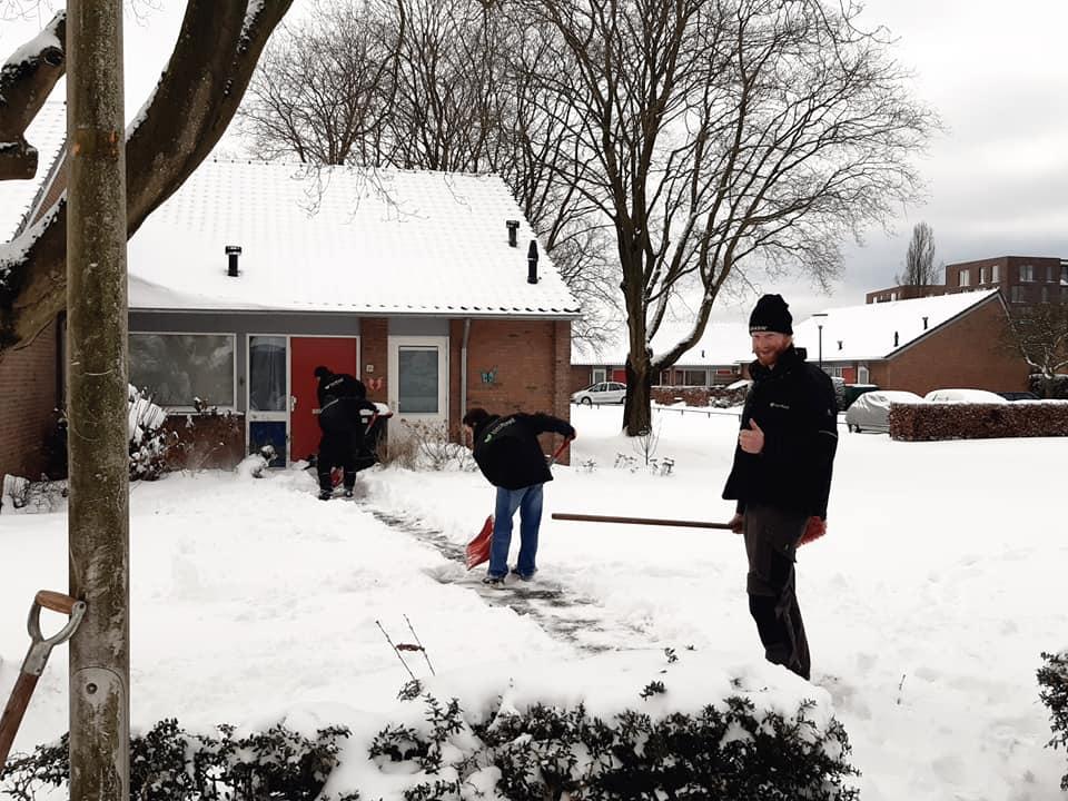 Jongeren die zijn vastgelopen helpen ouderen om hun oprit sneeuwvrij te maken