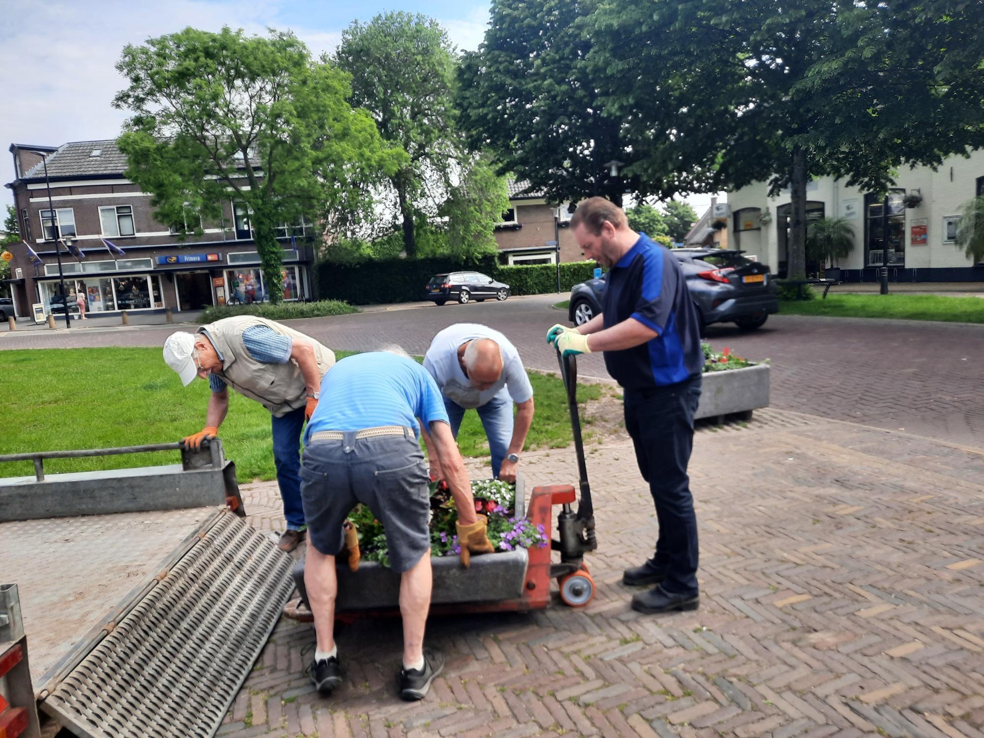 Vrijwilligers plaatsen bloembakken op Marktplein in Brummen