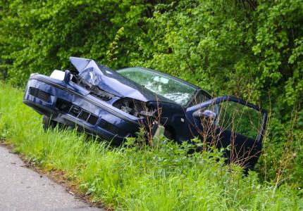 Auto belandt in greppel na botsing met boom; vrouw gewond